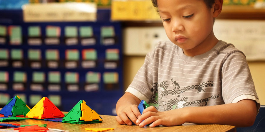 Young boy working with manipulatives.